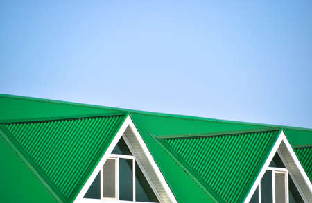 The house with plastic windows and a green roof of corrugated sheet. Roofing of metal profile wavy shape on the house with plastic windows. Stock Photo