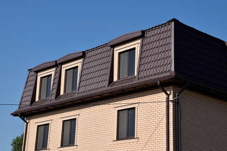 roof profile: The house with plastic windows and a roof of corrugated sheet. Roofing of metal profile wavy shape on the house with plastic windows. Stock Photo