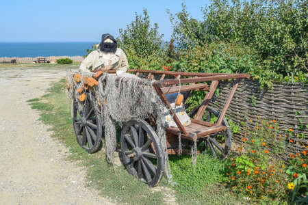 Mannequin fisherman in the wagon. The wagon with fishing nets and fisherman doll with a beard.