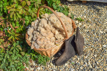 The wool in the basket and black boots. Sheared from sheep wool. 스톡 콘텐츠