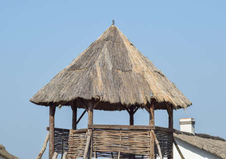 observant: Watchtower with a thatched roof. Wooden observation tower. Stock Photo