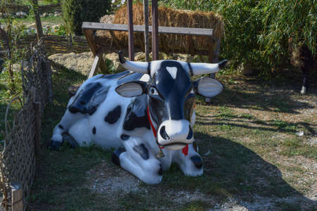 Large dummy cow. Black and white toy cow with a bell.
