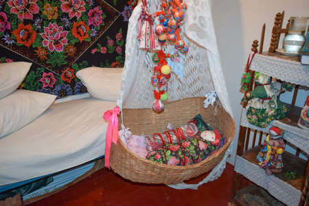 antiquity: Cradle with dolls in the bedroom. Homemade great toys for children. Recreating the image of antiquity. Stock Photo
