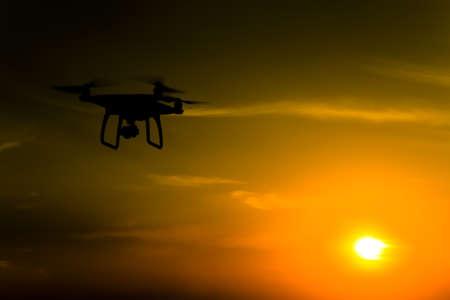 Silhouette Quadrocopters sur fond de coucher de soleil. Des drones volants dans le ciel du soir. Banque d'images - 64064167