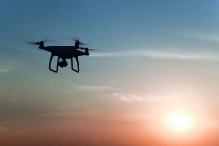 Quadrocopters silhouette against the background of the sunset. Flying drones in the evening sky.