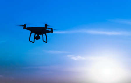 drones: Quadrocopters silhouette against the background of the sunrise. Flying drones in the evening sky.