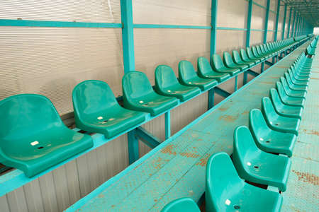 building sector: Rows of seats in an empty stadium. Green seats at the stadium.