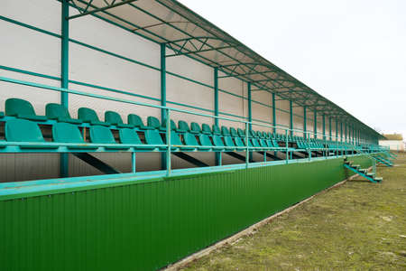 Rows of seats in an empty stadium. Green seats at the stadium.