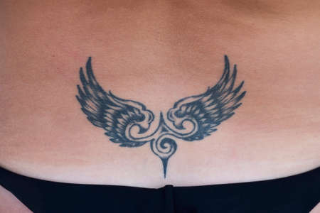 The tattoo in the shape of wings on the back. Simple tattoo for female body decoration.