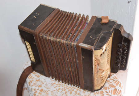 concertina: Old dusty accordion. Musical instruments of the Russian village.