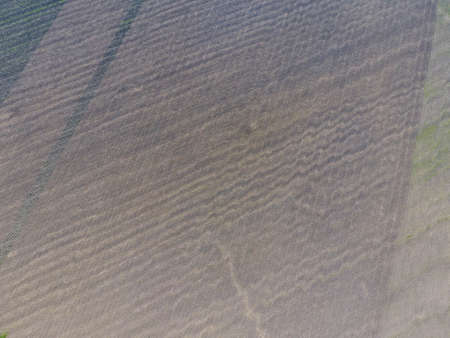 harrowing: Top view of a plowed field. Background texture of the surface of the plowed field. Shooting with quadrocopters. Stock Photo