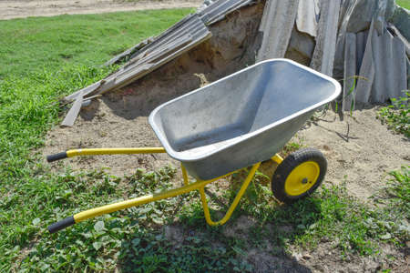Gardening Wheelbarrow For Transportation Of Sand And Earth. Two Wheel  Yellow Car. Stock