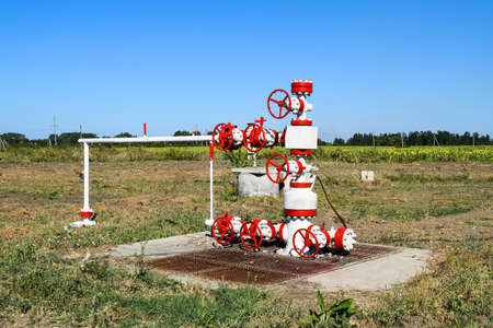 Oil well. The equipment and technologies on oil fields. Oil well in the field, painted in white and red. Oil with modern equipment. Stock Photo