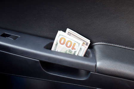 cash slips: Several notes of US dollars and are folded in half in the door handle of the car. The money in the car.