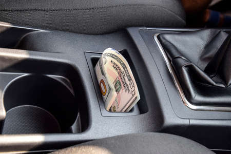 fraudulent: Several banknotes American dollars lie in the niche of the central console of the car. The money in the car.