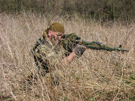 militiaman: Fighter of special troops. Sniper rifle hidden in dry grass, and aiming at a target.