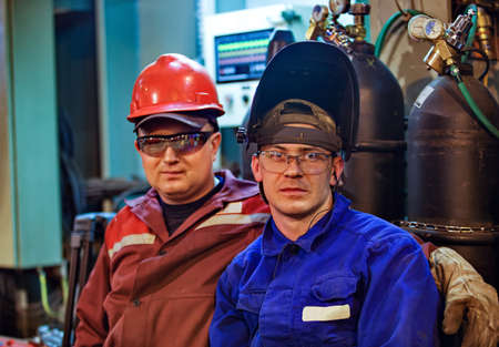Workers fitters and welders in protective clothing and a helmet. Working in the operating industrial facilities.