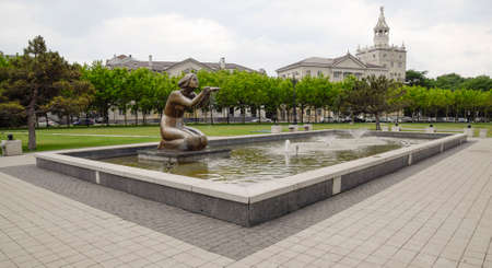 Statue of kneeling woman in the fountain. Water flowing from the hands of the statue. Stock Photo