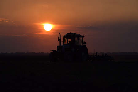 plowing: Tractor plowing plow the field on a background sunset. tractor silhouette on sunset background.