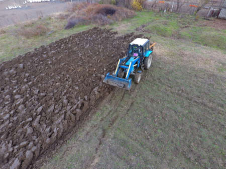 plowing: Tractor plowing the garden. Plowing the soil in the garden. Stock Photo