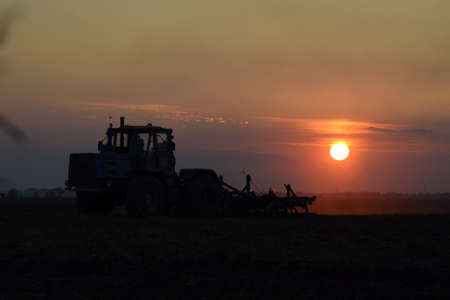 plough machine: Tractor plowing plow the field on a background sunset. tractor silhouette on sunset background.