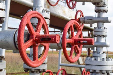 Shut-off valve valve with manual drive. Red steering wheel lock gate valve. oil well equipment. Stock Photo