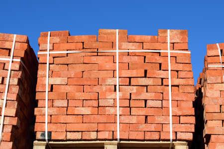 tiedup: Red bricks stacked into cubes. Warehouse bricks. Storage brickworks products.