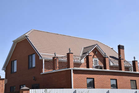 Detached house with a roof made of steel sheets. Roof metal sheets. Modern types of roofing materials. 免版税图像