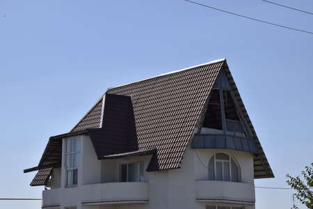 gable home renovation: Detached house with a roof made of steel sheets. Roof metal sheets. Modern types of roofing materials. Stock Photo