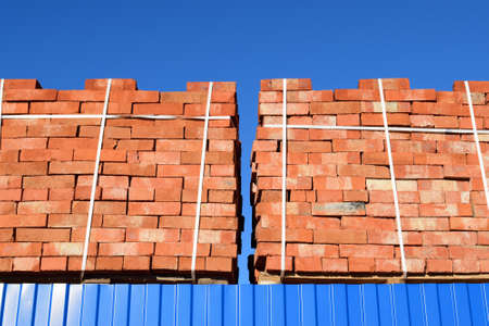 fastened: Red bricks stacked into cubes. Warehouse bricks. Storage brickworks products.