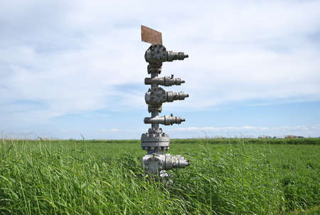 Canned oil well against the sky and field. Equipment of an oil well. Shutoff valves and service equipment. Stock Photo