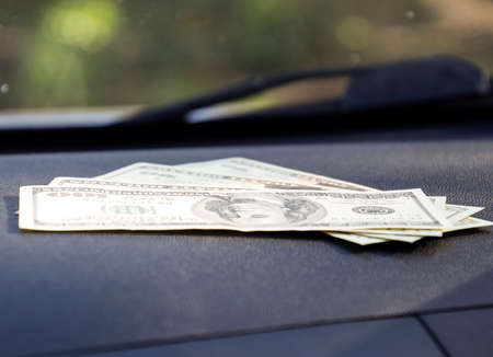 cash slips: Dollars on a car dashboard under the windshield. American Money.