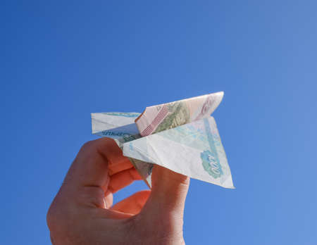 stock market launch: Denominations of Russian money, folded in the airplane against the blue sky in hand.