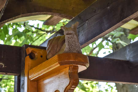 Statuette in the form of a snail on a wooden shelf under the canopy. Decoration of the restaurant.