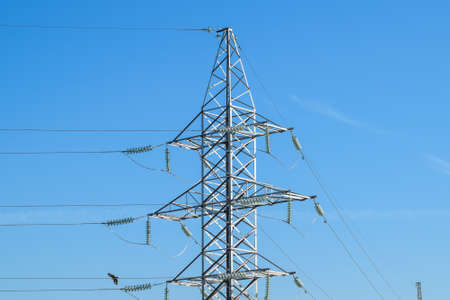 Supports high-voltage power lines against the blue sky. Stock Photo