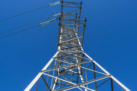 Supports high-voltage power lines against the blue sky. View from the bottom up.