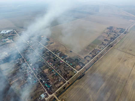 Top view of the small village. Smoke from the burning of straw is spread over the village