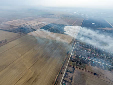 swelter: Top view of the small village. Smoke from the burning of straw is spread over the village