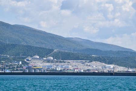 international seaports. Cargo port with port cranes. Sea bay and mountainous coast.