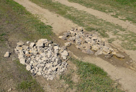 Road patching. Pits on the road are covered with stones. Stock Photo