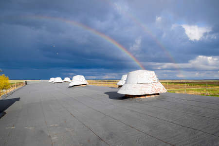 twice: Rainbow, view from the roof of the building. Ventilation outlets on the roof of the building. Stock Photo