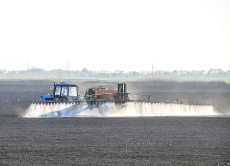 sprayed: The tractor sprayed herbicides on the field. Chemistry in agriculture. Stock Photo