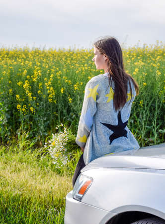 A girl with a bouquet of daisies sits on the hood of the car and looks into the distance