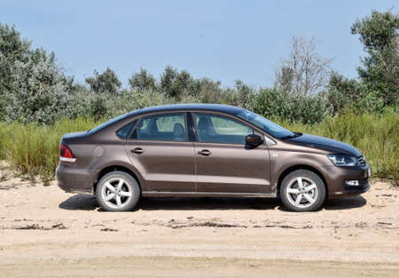 Anapa, Russia - July 17, 2017: Volkswagen Polo car on the beach in the sand against a background of vegetation. Editorial