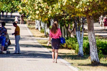 sidewalk talk: Novorossiysk, Russia - September 05, 2016: A blonde girl with a beautiful booty walking down the street.