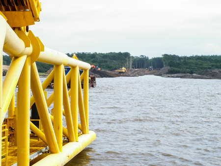 complex system: Descent of the pipeline to a bottom exhausting with the pipelaying barge. Installation of the underwater gas pipeline. Laying of pipes with pipe-laying barge crane near the shore