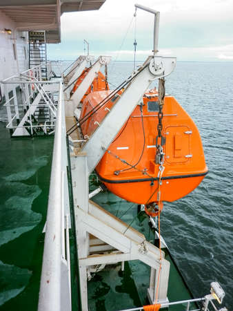 safe water: A lifeboat in case of an accident in the port or on a ship. The orange boat. Stock Photo