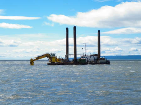 Barge with excavator. Excavator on the barge. Special vessel with a ladle and piles for anchoring on the ground. Stock Photo