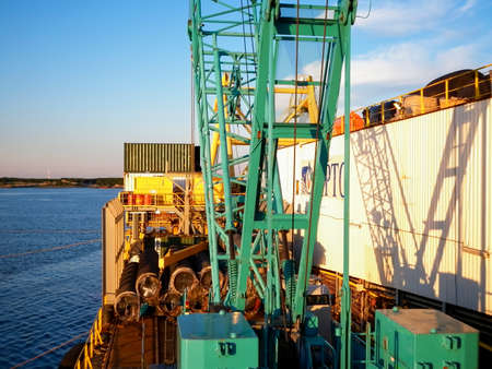 Baltic Sea, Russia - September 12, 2016: Lifting crane on the deck of a pipe laying barge. The type of port cranes in the background of the landscape of the port and port area.