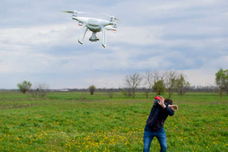 mounted: A man hides himself from a collision with a drone. Quadrocopter flies to the person. Stock Photo